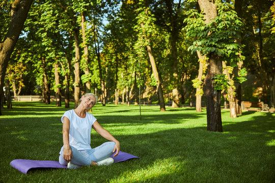 Beautiful smiling woman sitting on yoga mat outdoors