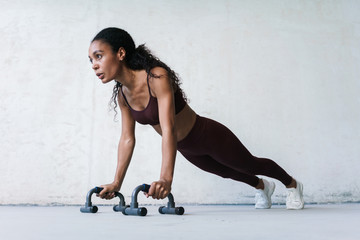 Photo of african american sportswoman working out with push-up stops