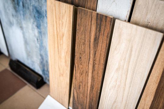 Variety of wooden like tiles. Samples of fake wood tiles for flooring. Assortment of floor laminate / tiles in an interior shop.