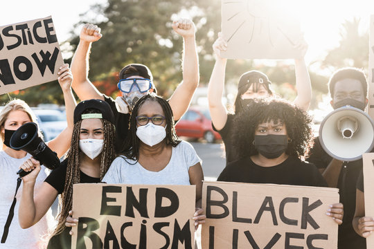 People from different ages and races protest on the street for equal rights - Demonstrators wearing protective masks during black lives matter no racism campaign - Focus on mature woman face