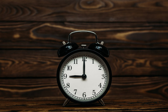 Clock on a wooden background. The clock shows the time of nine o'clock in the afternoon. The clock shows the time of nine o'clock in the morning. An image of a retro clock showing 09:00 pm/am.