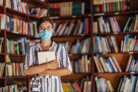 Portrait of young attractive college girl standing in library with face mask on holding a book. Studying during covid 19 concept.