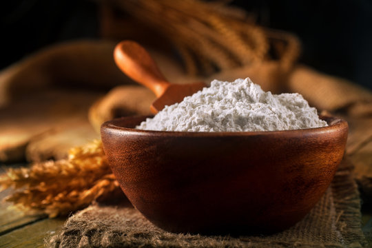 Flour in a bowl with a flour spoon, on a rustic wooden background. Close up, side view, high-resolution product image.