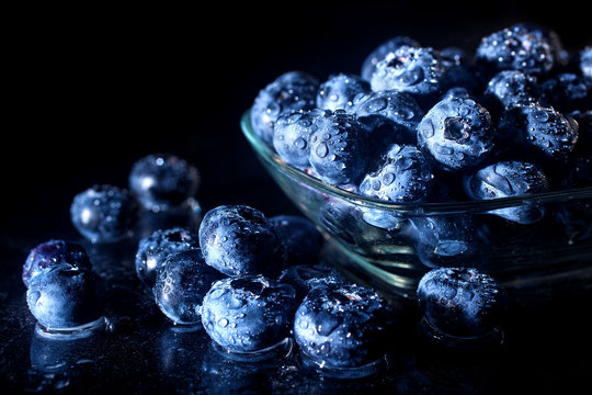 Freshly picked blueberries in a glass jar. Fresh and healthy juicy blueberries on a dark background. Blueberries as a fruit antioxidant symbol. Concept for healthy eating and nutrition.