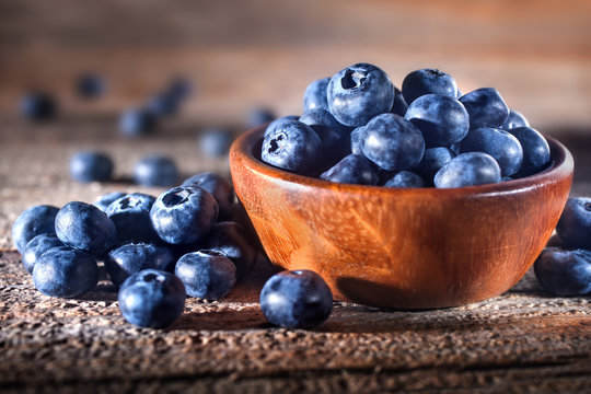 Freshly picked blueberries in a bowl. Fresh and healthy juicy blueberries on a rustic background. Blueberries as a fruit antioxidant symbol. Concept for healthy eating and nutrition.