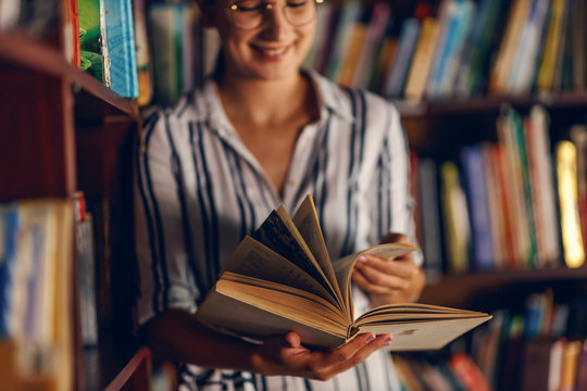 Young smiling attractive college girl leaning on book shelves in library and searching for material for homework.