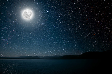 Wall Mural - moon against a bright night starry sky reflected in the sea.
