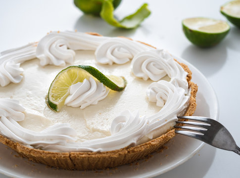 Keylime pie and fresh limes on a white table.