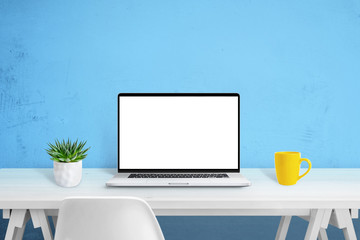 Wall Mural - Laptop computer mockup on white wooden desk. Creative scene with plant and yellow coffee mug and blue wall in background