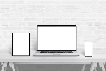 Wall Mural - Devices with isolated screens for responsive web design promotion. Web design studio concept on white wooden desk and brick wall in background