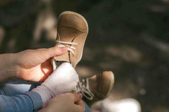 A young mother puts on a one-year-old toddler on a walk boots. The first shoe for a child, quality and comfort