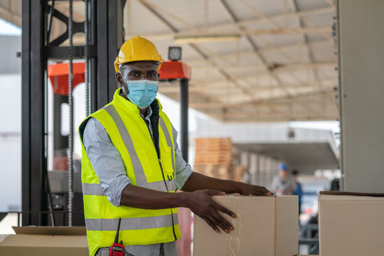 Man worker wear face mask in safety vest and yellow helmet preparing product input to box for shipment at warehouse factory