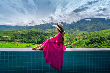 Wall Mural - Woman enjoying rice terrace viewpoint and green forest in Nan, Thailand.