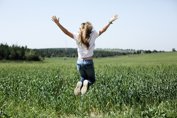 Girl is jumping in the field