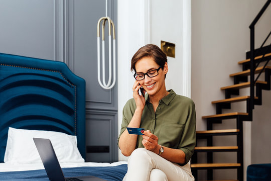 Smiling woman sitting on a bed with laptop and credit card talking over mobile phone