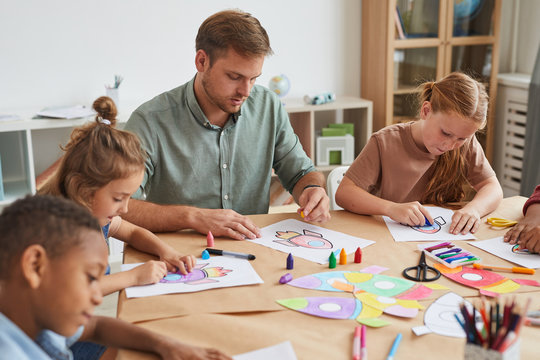 Portrait of male teacher working with multi-ethnic group of children drawing pictures during art class in school or development center, copy space