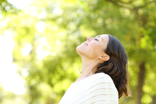 Mid age woman breathing fresh air in the forest