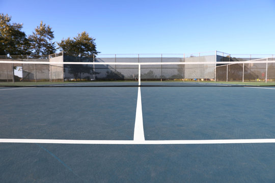 A view of a tennis court from the baseline