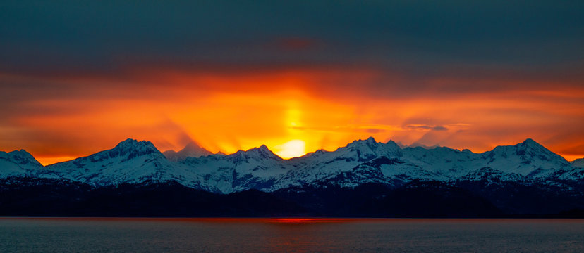 Beautiful Panorama Golden Hour Alaskan Sunset over Mountains from the Ocean with a Sun Pillar