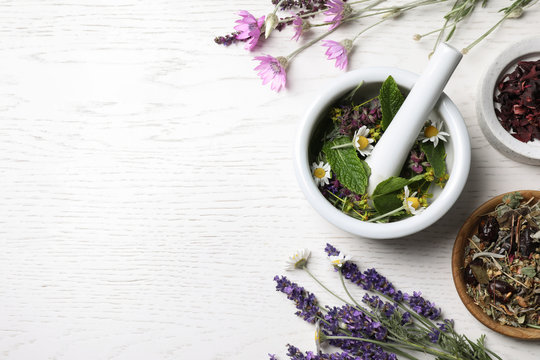 Mortar with healing herbs and pestle on white wooden table, flat lay. Space for text