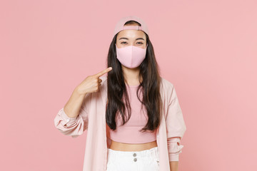 Young asian woman girl in casual clothes cap posing isolated on pastel pink background. Epidemic pandemic coronavirus 2019-ncov sars covid-19 flu virus concept. Pointing index finger on face mask.