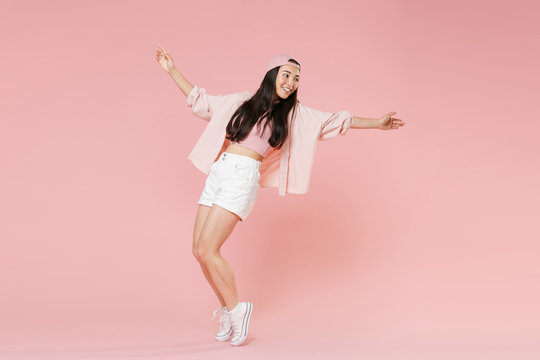 Full length portrait of funny young asian girl in casual clothes, cap isolated on pastel pink background studio. People lifestyle concept. Mock up copy space. Dancing spreading hands standing on toes.