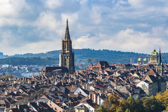 Stunning aerial view of Bern old town with Bern Minster (Münster) cathedral and Swiss Federal Palace (Bundeshaus), from Rosengarten on sunny autumn day, Switzerland
