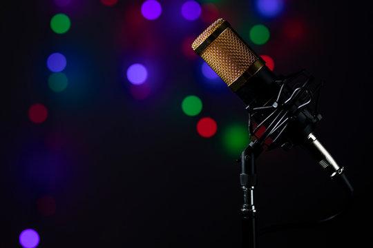 Micrófono profesional de mesa con cable y montado en su base, con luces de colores en el fondo.