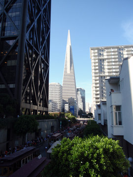 trolleys and people line up for the start of parade with the Transamerica Pyramid in distance