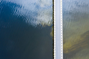 bridge over lake. clouds are reflected in the smooth surface of water on sunny day. aerial top view
