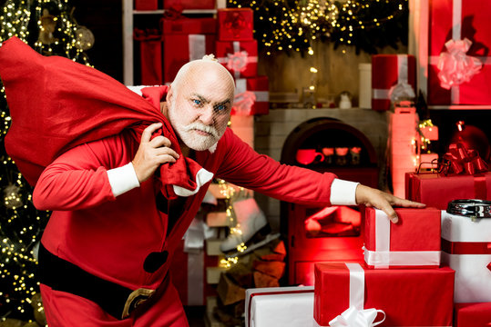 Thief stole new years presents. Criminal christmas. Criminal Santa Claus posing with a bag of christmas gifts.