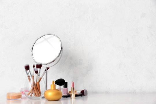 Set of makeup cosmetics with brushes and mirror on table
