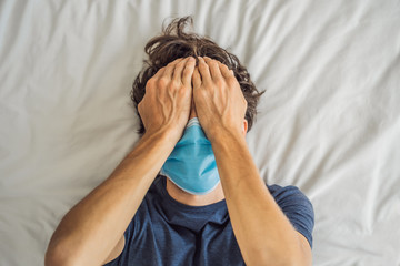 Extremly tired young man lying on the bed, home alone. self-isolation at home, quarantine due to...