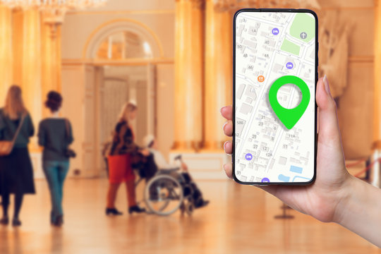 A females hand holds a smartphone with an online map on the screen. In the background, a group of people and a man in a wheelchair in a Museum, in a blur. Concept of online applications and navigation