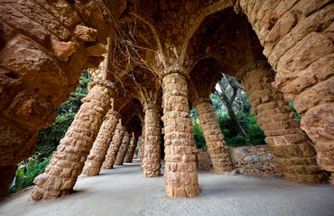 Barcelona, Spain. Park Guell. Antonio Gaudi Art Architecture. Stone pillars with archs at sunset among green trees and plants. Famous touristic destination landmark for walking tours. Fotobehang