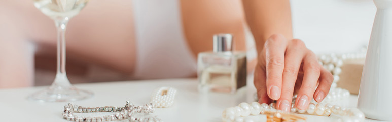 Panoramic crop of bride touching pearl necklace near accessories on coffee table