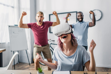 Selective focus of businesswoman in vr headset showing yes with multicultural colleagues at background