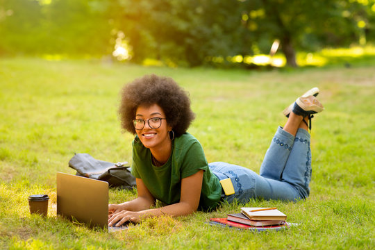 Black College Student Girl Studying With Laptop Outdoors, Lying On Lawn
