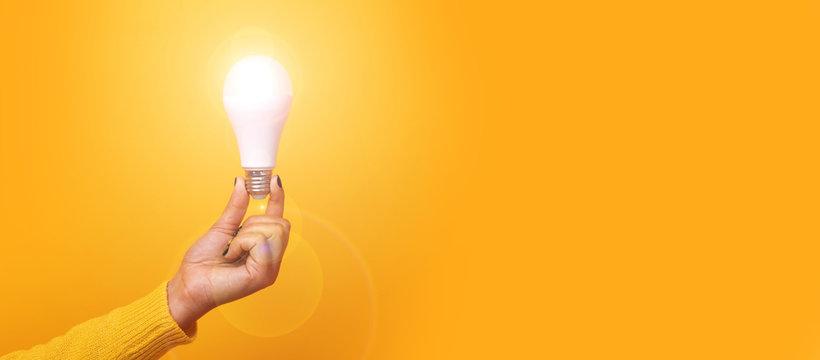 hand holding light bulb, illuminated light bulb, panoramic mock up over yellow background