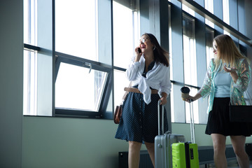 Stylish. Young women waiting for departure in airport, traveler with small baggage, influencer's or blogger's lifestyle. Caucasian female model with gadgets before starting her vacation, registration.