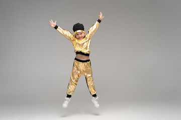 Happy little girl in gold suit dancing isolated on white background