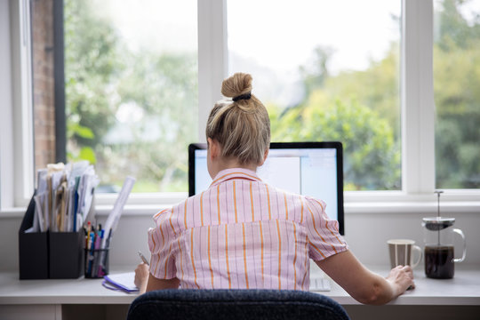 Rear View Of Woman Working From Home On Computer  In Home Office