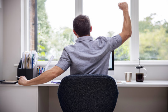 Rear View Of Man Working From Home On Computer  In Home Office Stretching At Desk