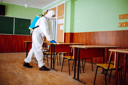 A man from disinfection group cleans up the desk at school with a yellow rag. Professional worker sterilizes the classroom to prevent covid-19 spread. Healthcare of pupils and students concept.