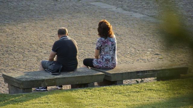 Mann und Frau auf Parkbank sitzend. Rückansicht.