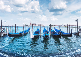 Colorful landscape with clear blue sky on piazza San Marco in Venice. Row of gondolas parked on city pier. Church of San Giorgio Maggiore on background, Italy, Europe