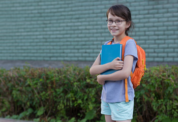 Happy girl with backpack and books going to school. Education and study. Knowledge day.