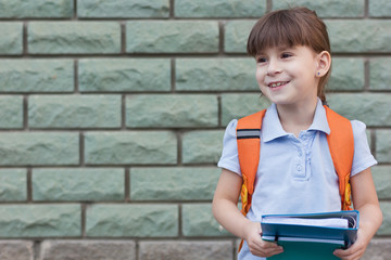 Happy little child hoiding notebooks. Portrait of  little schoolgirl isolated on a brick green wall