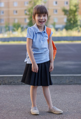 Portrait of happy little girl with backpackon a school yard. Education and study. Knowledge day.