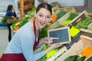 female fruit and vegetable seller holding board
